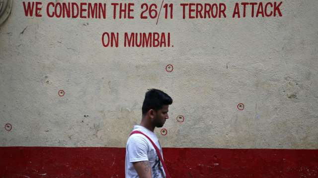 Wall riddled with bullet holes opposite Nariman House