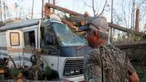 A man looks over the damage to his RV caused by Hurricane Michael in St. Andrews Bay, Florida, October 16, (Reuters)